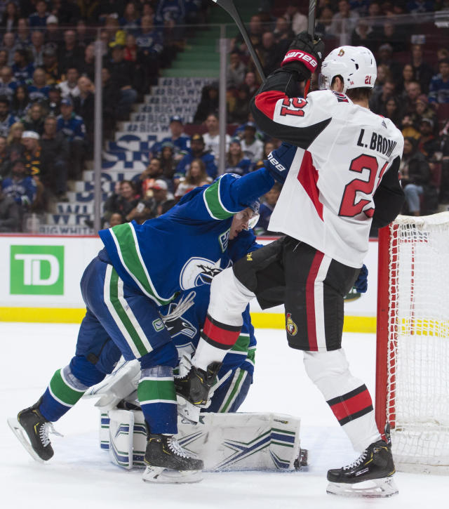 Vancouver Canucks defenseman Troy Stecher (51) clears Ottawa Senators center Logan Brown (21) from in front of goaltender Thatcher Demko during the third period of an NHL hockey game Tuesday, Dec. 3, 2019, in Vancouver, British Columbia. (Jonathan Hayward/The Canadian Press via AP)