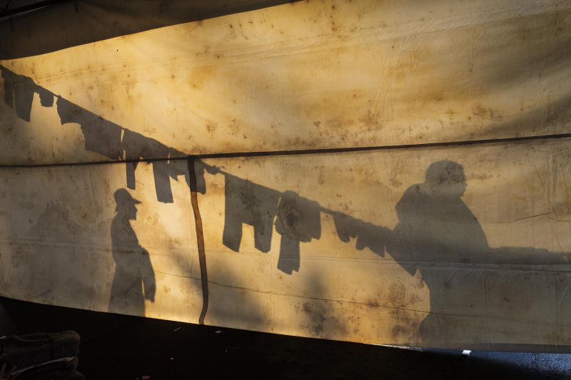 In this Nov. 6, 2018 photo, the silhouettes of Central American migrants are projected on the side of a tent at the Jesus Martinez stadium in Mexico City. Humanitarian aid converged around the stadium in Mexico City where thousands of Central American migrants winding their way toward the United States were resting Tuesday after an arduous trek that has taken them through three countries in three weeks. (AP Photo/Rodrigo Abd)