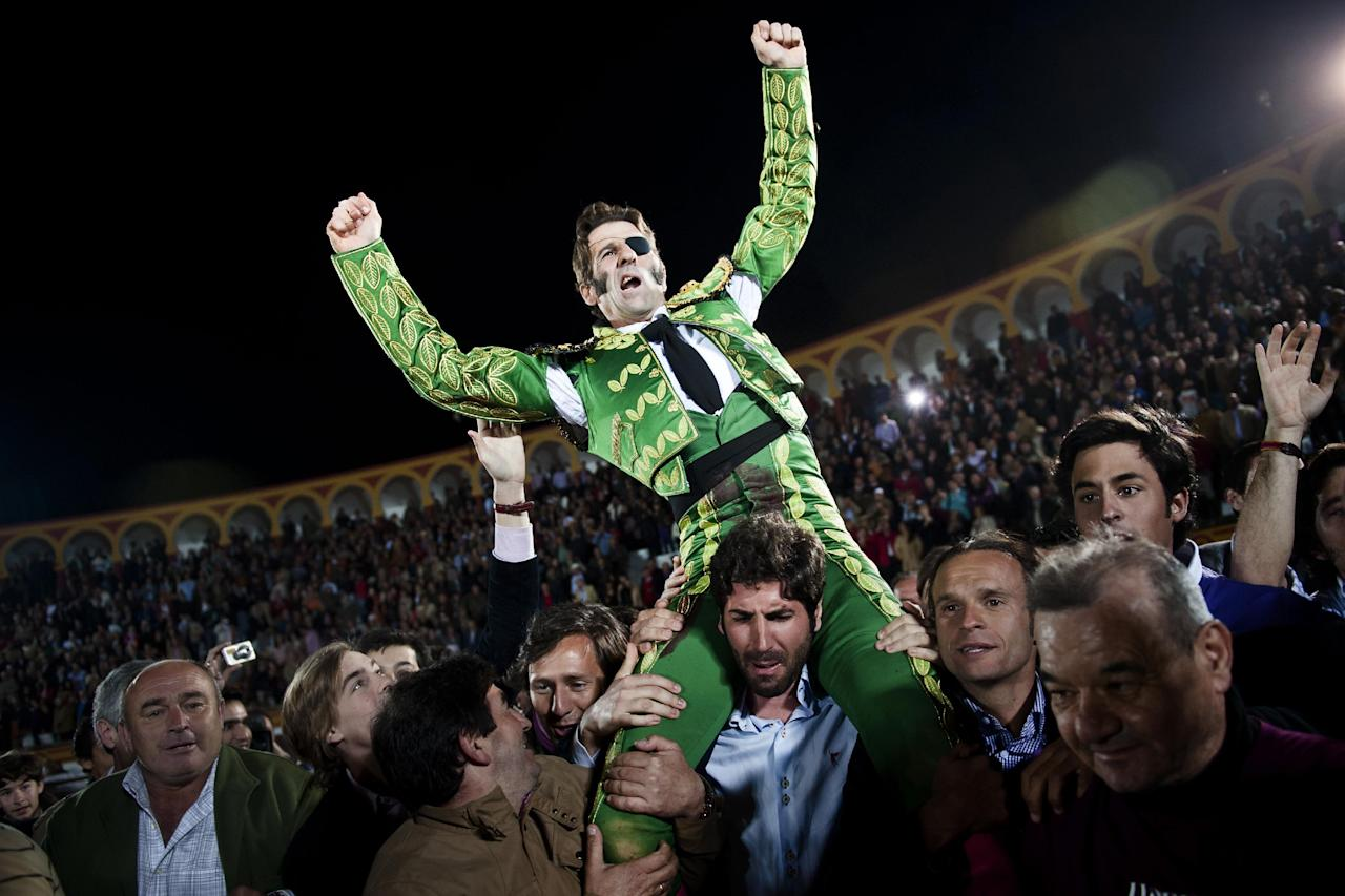 Spanish bullfighter Juan Jose Padilla is carried out of the ring among jubilant crowd scenes on the shoulders of fellow bullfighter Serafin Marin, a honor for the best performers, after a bullfight at the southwestern Spanish town of Olivenza, Sunday, March 4, 2012. Padilla, 38-year-old matador who is also known by his professional name of 'the Cyclone of Jerez', lost sight in one eye and has partial facial paralysis after a terrifying goring returned to the bullring Sunday, five months after his injury.(AP Photo/Daniel Ochoa de Olza)