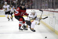 Vegas Golden Knights left wing Tomas Nosek (92), of the Czech Republic, hits the ice while competing for the puck with New Jersey Devils defenseman Will Butcher (8) during the first period of an NHL hockey game, Friday, Dec. 14, 2018, in Newark. (AP Photo/Julio Cortez)