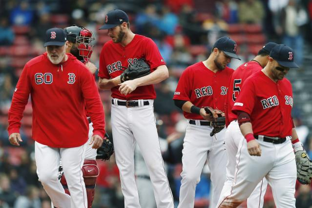 Boston Red Sox pitching coach Dana LeVangie, left, walks back to the dugout after a conference on the mound with Chris Sale, center, during the fifth inning of the first game of a baseball doubleheader against the Detroit Tigers in Boston, Tuesday, April 23, 2019. (AP Photo/Michael Dwyer)
