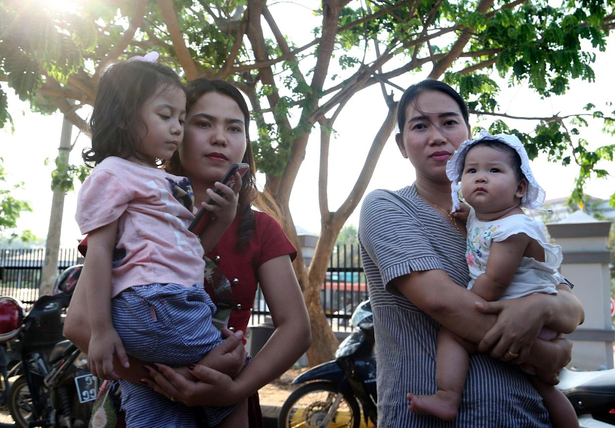 Chit Su Win, wife of Reuters journalist Kyaw Soe Oo, left, and Pan Ei Mon, right, wife of Reuters journalist Wa Lone, hold their children as they leave the Supreme Court in Myanmar. (Photo: Aung Shine Oo/AP)