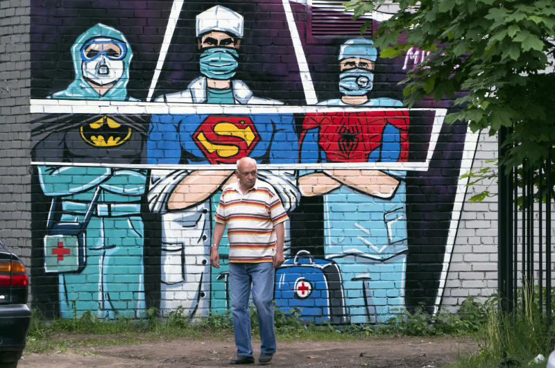 A man walks past a graffiti depicting medical workers struggling with coronavirus as superheroes in Vsevolozhsk, outside St.Petersburg, Russia, Monday, June 15, 2020. (AP Photo/Dmitri Lovetsky)