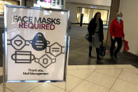 """FILE - In this Nov. 13, 2020, file photo, a """"Face masks required"""" sign is displayed at a shopping center in Schaumburg, Ill. States in the U.S. are renewing their push for more federal money to deal with the fallout from the coronavirus outbreak and to help them distribute a vaccine when one becomes widely available sometime in 2021. (AP Photo/Nam Y. Huh, File)"""
