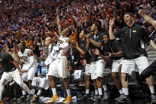 Virginia Commonwealth forward Mo Alie-Cox, center left, raises his hand with three fingers up after teammate Jordan Burgess sinks a 3-point basket as he watches from the bench while playing Stephen F. Austin during the second half of a second-round game in the NCAA college basketball tournament Friday, March 21, 2014, in San Diego. (AP Photo/Lenny Ignelzi)