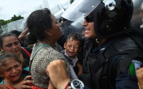 Honduran migrants heading in a caravan to the US, hold up a crying baby while they struggle to cross one of the gates of the Guatemala-Mexico international border bridge in Ciudad Hidalgo - Credit: AFP
