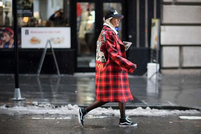 <p>This street style star embodies a skater-girl style that you can easily replicate. A plaid coat is a great option for those looking to opt out of another neutral look. Pair it with a baseball cap, tights, and your favorite Vans. (Photo: Getty Images) </p>