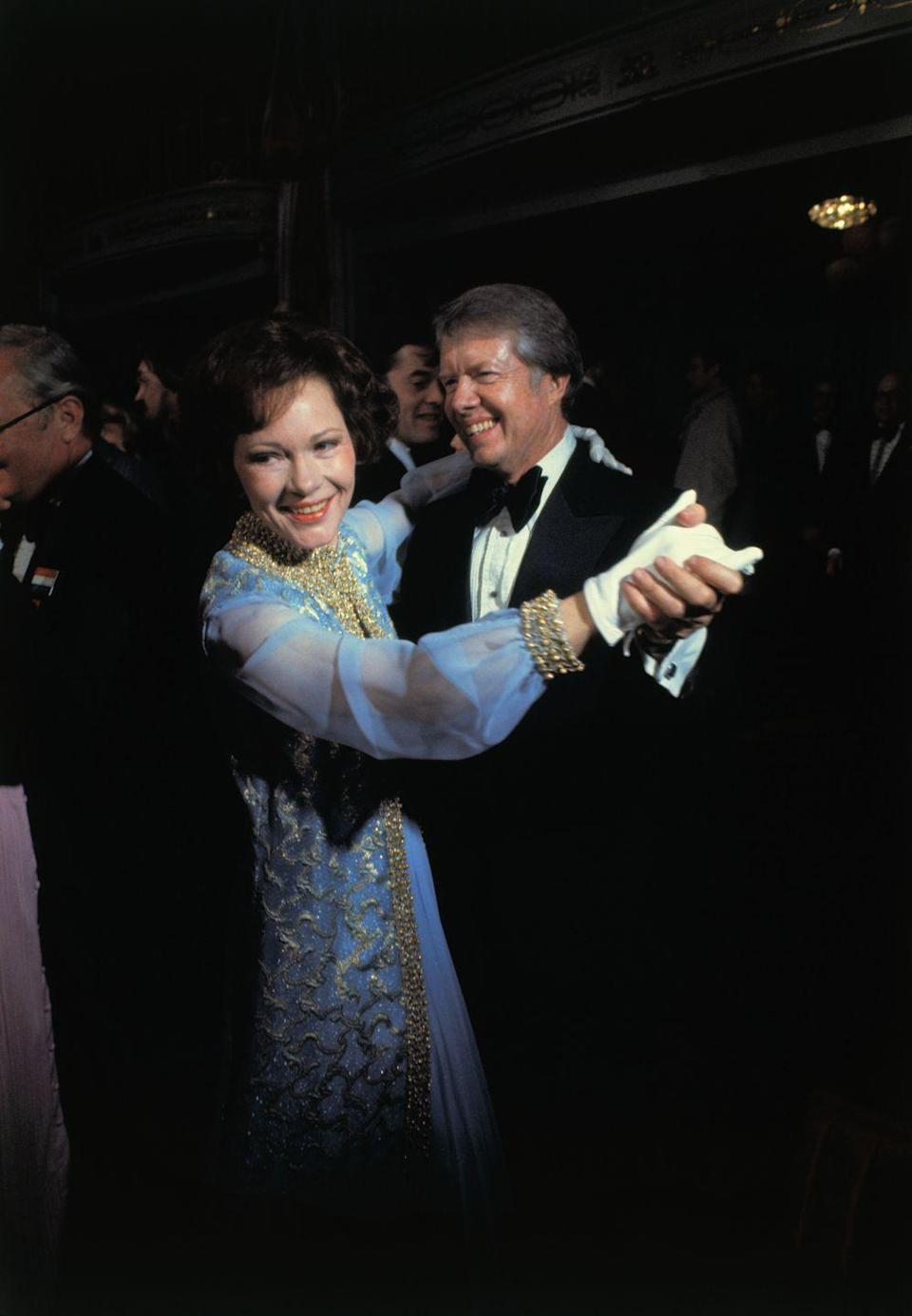 """<p>The couple share a dance at the inaugural ball in 1977. Rosalynn Carter wears an elaborate blue chiffon evening gown with gold brocade detailing. Her dress and jacket were <a href=""""https://americanhistory.si.edu/first-ladies/rosalynn-carter"""" rel=""""nofollow noopener"""" target=""""_blank"""" data-ylk=""""slk:designed by Mary Matise for Jimmae"""" class=""""link rapid-noclick-resp"""">designed by Mary Matise for Jimmae</a>. </p>"""