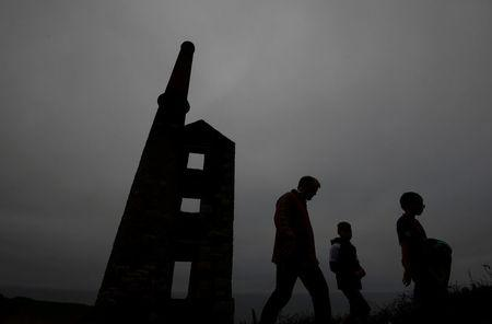 FILE PHOTO: A family walk past the remains of the engine house at the Wheal Prosper copper and tin mine near Porthleven in Cornwall
