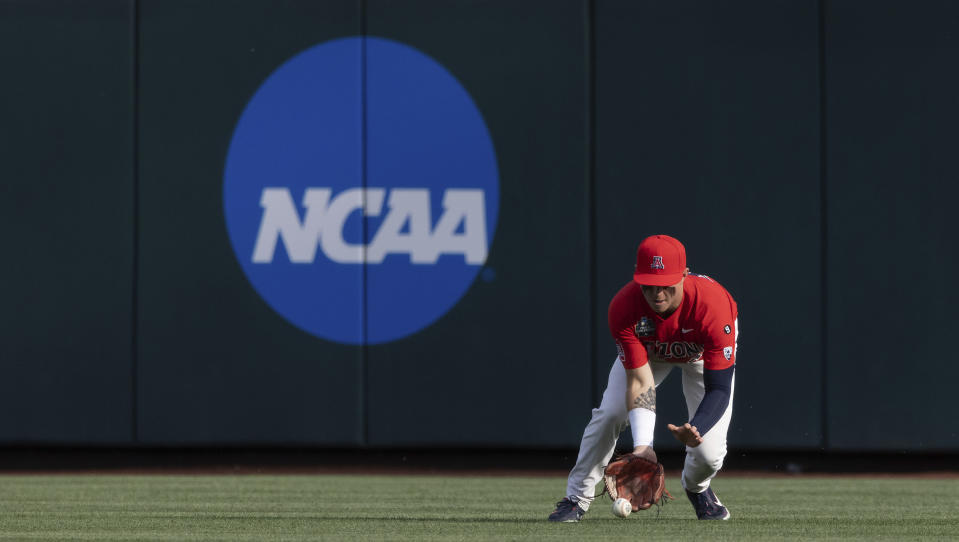 Arizona's Ryan Holgate fields a hit by Vanderbilt's Dominic Keegan during the first inning of a baseball game in the NCAA College World Series on Saturday, June 19, 2021, in Omaha, Neb. (AP Photo/Rebecca S. Gratz)
