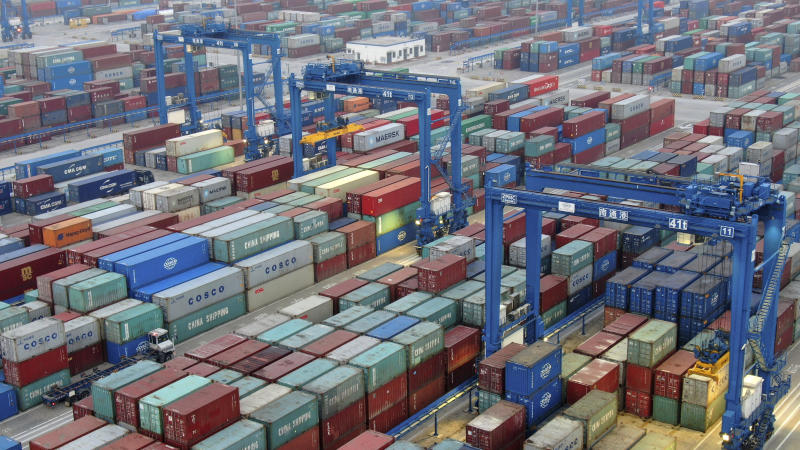 In this Tuesday, Jan. 14, 2020 photo, shipping containers are stacked at a dockyard on the Yangtze River in Nantong in eastern China's Jiangsu Province. China's economic growth sank to a new multi-decade low in 2019 as Beijing fought a tariff war with Washington, but forecasters said a U.S.-Chinese trade truce might help to revive consumer and business activity. (Chinatopix via AP)