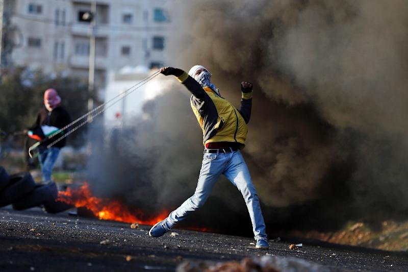 A Palestinian demonstrator uses a slingshot to hurl rocks at Israeli security forces during clashes following a demonstration against Israeli occupation, in the town of al-Bireh on the outskirts of Ramallah in the West Bank, on November 29, 2015 (AFP Photo/Abbas Momani)