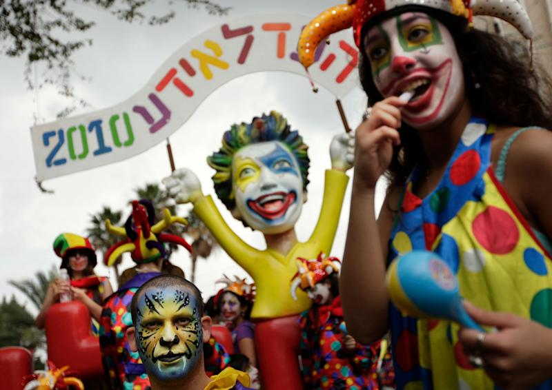 Israelis in costumes and masks dance in the street during the annual Purim parade in Holon, near Tel Aviv, Israel, Monday, March 1, 2010. (AP Photo/Ariel Schalit)