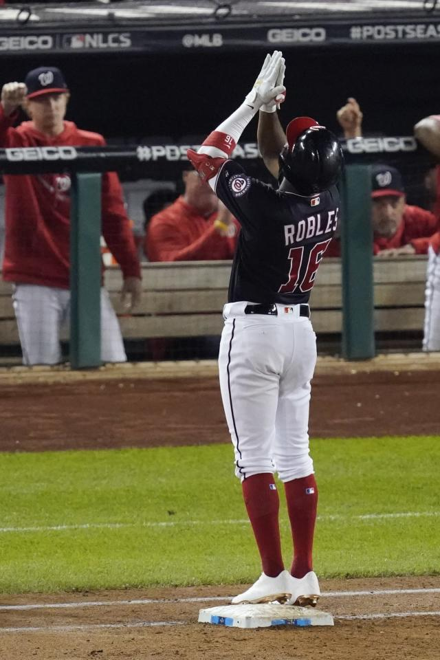 Washington Nationals' Victor Robles reacts after hitting a single during the third inning of Game 3 of the baseball National League Championship Series against the St. Louis Cardinals Monday, Oct. 14, 2019, in Washington. (AP Photo/Alex Brandon)