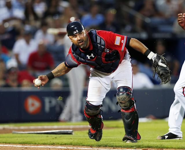 Atlanta Braves catcher Gerald Laird fields a ball in front of the plate and throws out Arizona Diamondbacks' Nick Ahmed in the third inning of a baseball game in Atlanta, Friday, July 4, 2014. (AP Photo/John Bazemore)