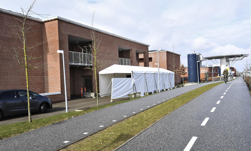 A tent serves as a drive-thru coronavirus testing facility at Aarhus University Hospital in Aarhus, Denmark, Monday March 9, 2020.  Locals are able to drive though the tented corridor, and met by a hospital worker who performs the COVID-19 test without the driver leaving their car. (Ernst van Norde/Ritzau via AP)