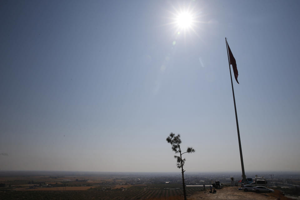 A Turkish flag on a hilltop at the Turkey-Syria border in the town of Ceylanpinar, Sanliurfa province, southeastern Turkey, Wednesday, Oct. 23, 2019, overlooking the town of Ras al-Ayn, Syria. Russian media reports say Russian military police have started patrols in northern Syria as a Turkish-Russian agreement giving Syrian Kurdish fighters 150 hours to withdraw from almost the entire northeast border region of Syria came into effect. (AP Photo/Lefteris Pitarakis)