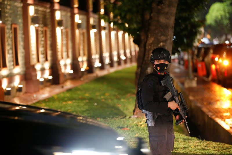 Armed police officer stands guard outside national police headquarters, in Jakarta
