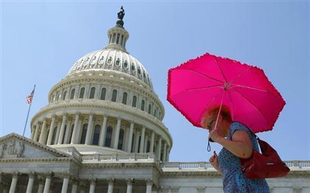 A woman holds an umbrella against the hot sun in Washington