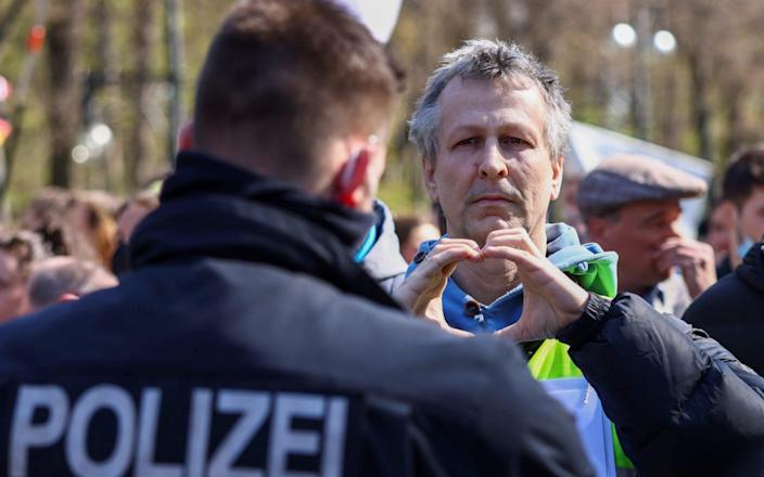 A man gestures to the police as he takes part in a protest against the government measures to curb the spread of the coronavirus disease, as the lower house of parliament Bundestag discusses additions for the Infection Protection Act, in Berlin, Germany - Christian Mang/Reuters