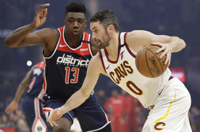 Cleveland Cavaliers' Kevin Love, right, drives past Washington Wizards' Thomas Bryant in the first half of an NBA basketball game, Thursday, Jan. 23, 2020, in Cleveland. (AP Photo/Tony Dejak)