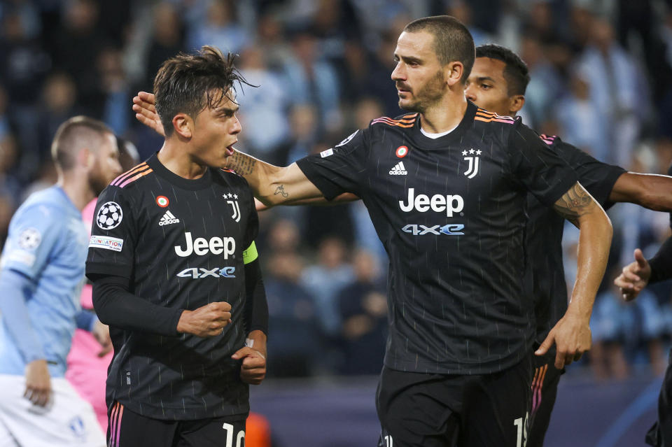Juventus' Paulo Dybala, left, celebrates scoring a penalty with teammate Leonardo Bonucci during the Champions League group H soccer match between Malmo FF and Juventus FC at Malmo New Stadium in Malmo, Sweden, Tuesday, Sept. 14, 2021. (Andreas Hillergren/TT News Agency via AP)