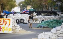 A woman walks past barricades set up by anti-government protesters near Government House in Bangkok February 17, 2014. Thousands of protesters seeking to oust Thai Prime Minister Yingluck Shinawatra surrounded the government's headquarters in Bangkok on Monday, in a defiant riposte to police efforts to begin retaking sites they have been occupying for weeks. REUTERS/Athit Perawongmetha(THAILAND - Tags: POLITICS CIVIL UNREST)