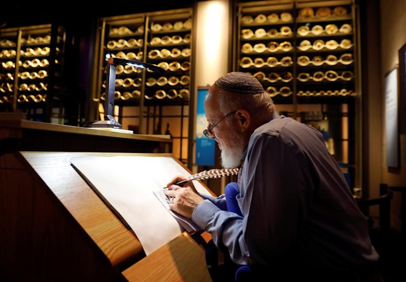 With ancient scrolls as a backdrop, Israeli Eliezer Adam works with ink and feather copying the Five Books of Moses, which he says will take a year, at the Museum of the Bible in Washington on Nov. 14. (Kevin Lamarque/Reuters)