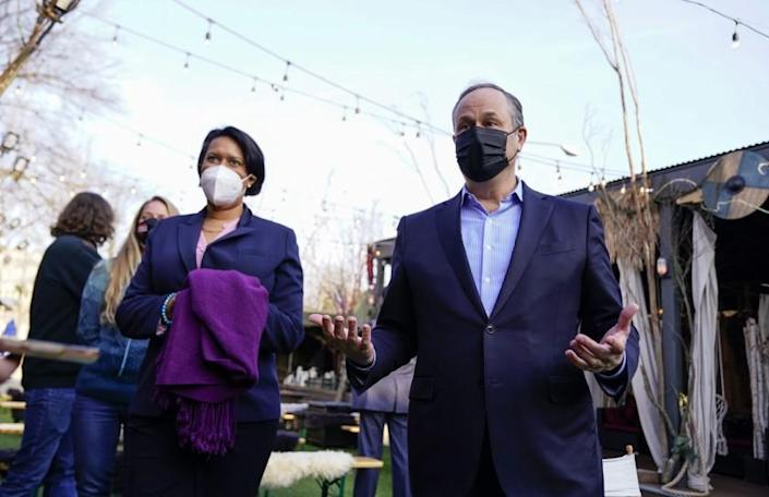 """Doug Emhoff, husband of Vice President Kamala Harris, talks with members of the press as he and Washington Mayor Muriel Bowser, left, tour """"Hook Hall Helps"""" a COVID-19 relief effort that organizes and distributes prepared meals and care kits to local hospitality workers whose jobs have been impacted by pandemic-related shutdowns and restrictions, during a visit to the organization in Washington, on Monday, March 8, 2021. (Erin Scott/Pool via AP)"""