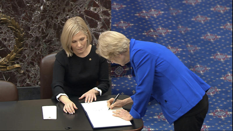 In this image from video, Sen. Elizabeth Warren, D-Mass., signs the oath book after being sworn in for the impeachment trial of President Donald Trump in the Senate at the U.S. Capitol in Washington, Thursday, Jan. 16, 2020. (Senate Television via AP)
