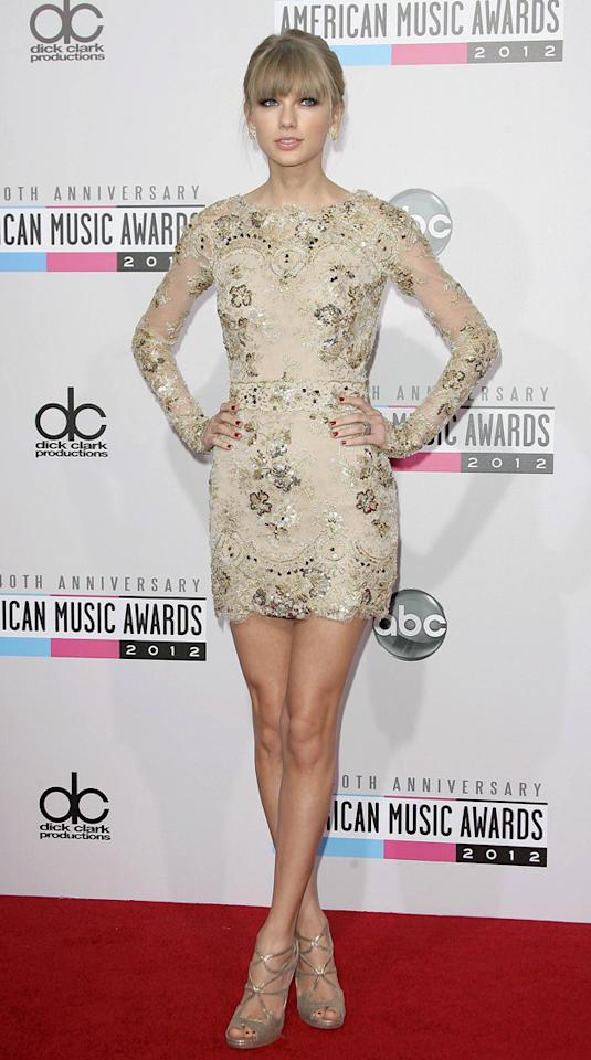 AMAs 2012: Taylor Swift looked incredible in this lace long-sleeved embellished mini dress. We cannot get over those legs. Taylor also walked away with the best Country artist gong, which we reckon is well deserved. Copyright [WENN]
