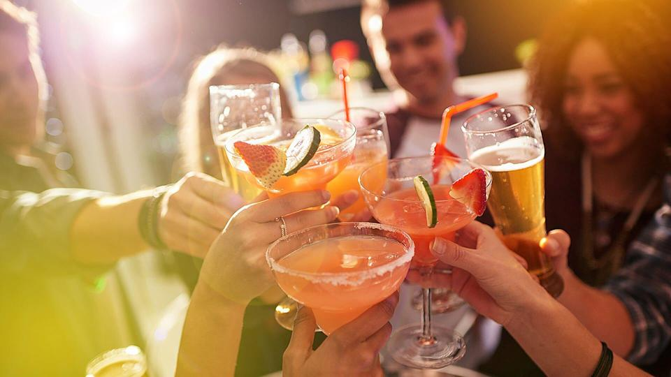 Shot of a group of people toasting with their drinks at a nightclub.