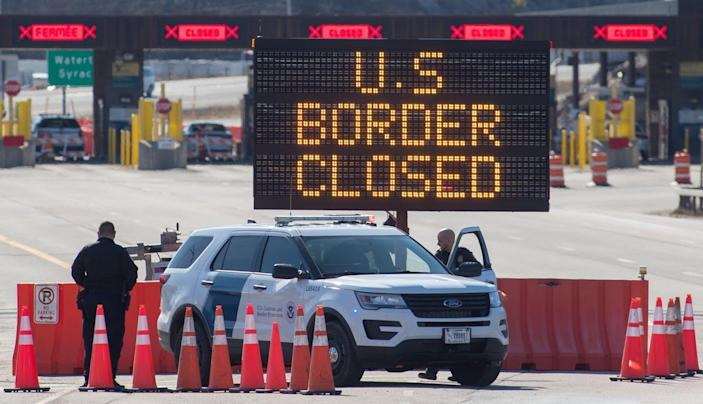 """<span class=""""caption"""">U.S. Customs officers stand beside a sign at the US/Canada border in Lansdowne, Ontario, on March 22, 2020.</span> <span class=""""attribution""""><a class=""""link rapid-noclick-resp"""" href=""""https://www.gettyimages.com/detail/news-photo/customs-officers-stand-beside-a-sign-saying-that-the-us-news-photo/1207963430?adppopup=true"""" rel=""""nofollow noopener"""" target=""""_blank"""" data-ylk=""""slk:Lars Hagberg / AFP via Getty Images"""">Lars Hagberg / AFP via Getty Images</a></span>"""