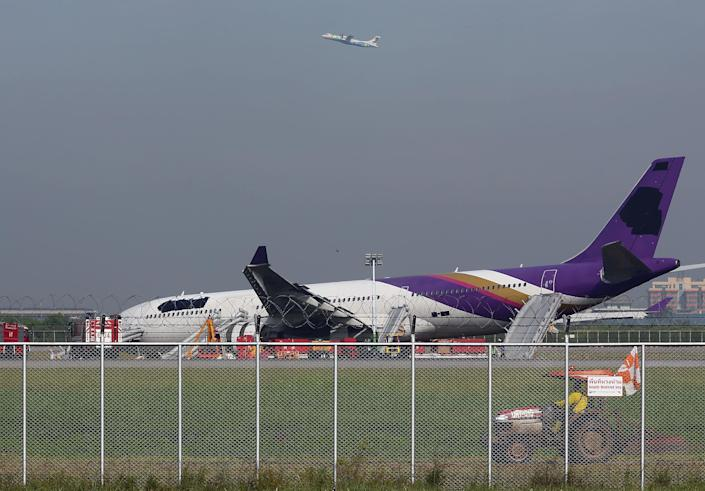 An airport worker drives a cart by a damaged Thai Airways Airbus A330-300 as a passenger planer takes off at Sunvarnabhumi International Airport in Bangkok, Thailand Monday, Sept. 9, 2013. The plane carrying more than 280 people skidded off the runway while landing Sunday, injuring 14 passengers. After the accident, workers on a crane blacked out the Thai Airways logo on the tail and body of the aircraft. (AP Photo/Apichart Weerawong)