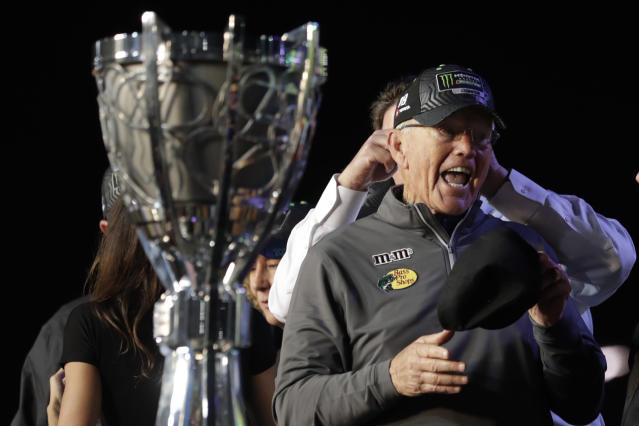 Team owner Joe Gibbs stands next to the championship trophy after his driver Kyle Busch won a NASCAR Cup Series auto racing season championship at Homestead-Miami Speedway in Homestead, Fla., Sunday, Nov. 17, 2019. (AP Photo/Luis M. Alvarez)