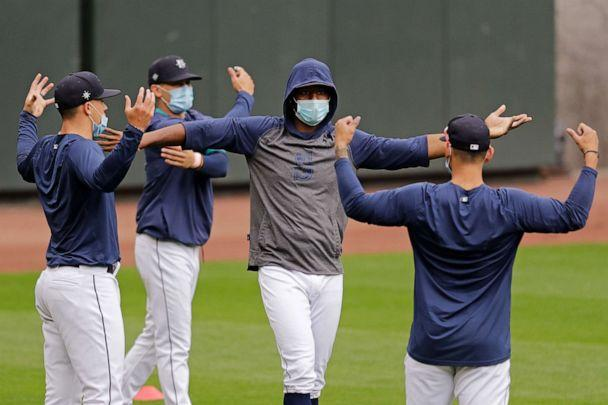 PHOTO: Seattle Mariners outfielder Kyle Lewis, center right, stretches with teammates at baseball practice in Seattle, July 7, 2020. (Elaine Thompson/AP)