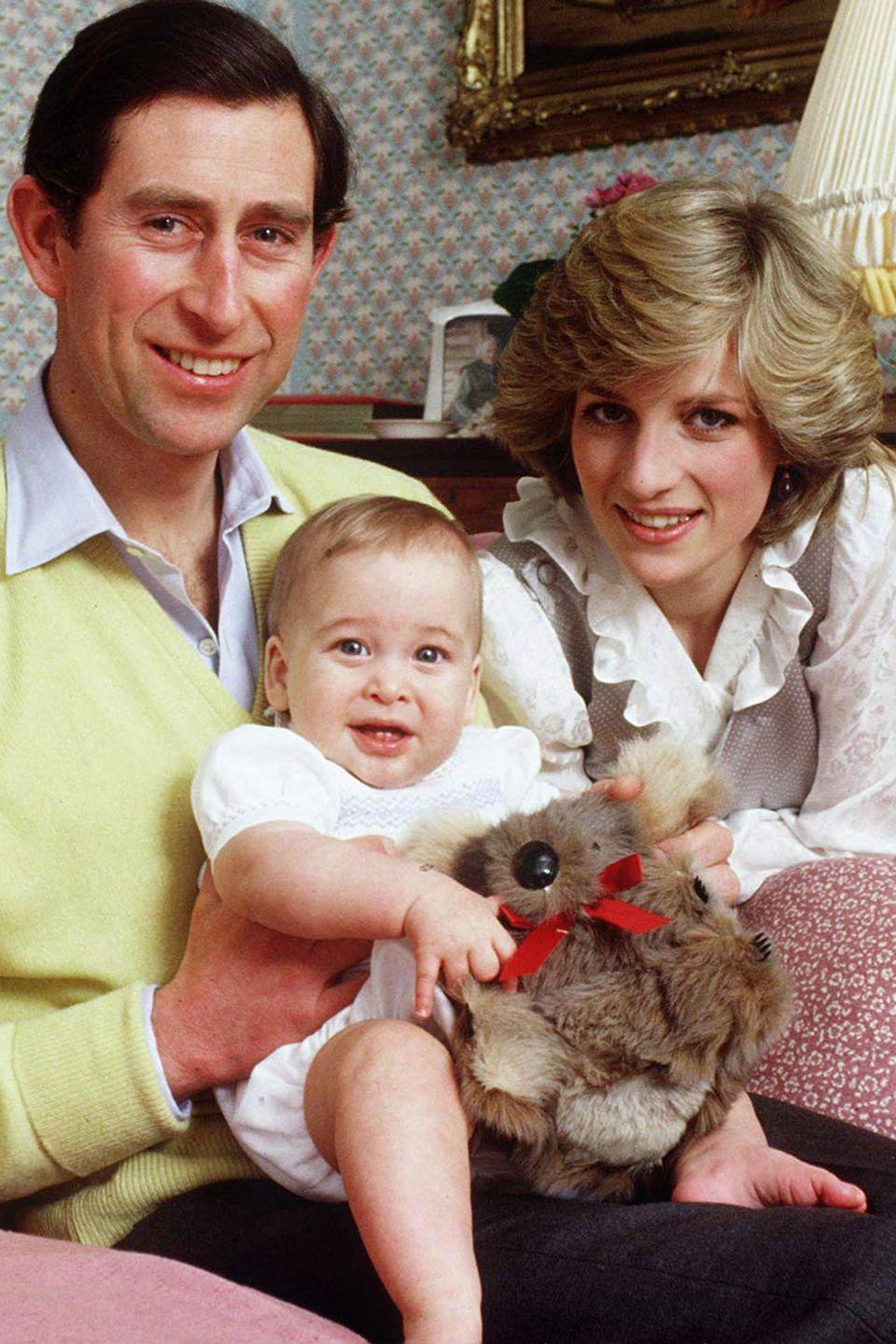 <p>Prince Charles, Princess Diana, and Prince William (holding a toy koala) pose for a family photo at Kensington Palace. </p>