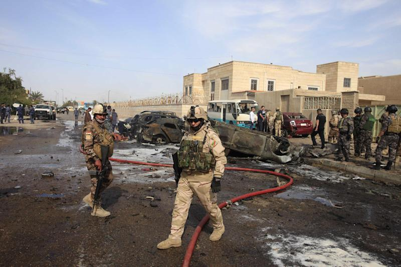 Civilians and security forces personnel gather at the scene of a car bomb attack in Baghdad, Iraq, Friday, March 29, 2013. A string of bombings targeting Shiite mosques on Friday, killing and wounding dozens of people, police said.(AP Photo/Karim Kadim)