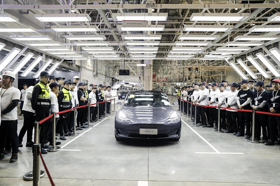 A Tesla Model 3 vehicle set to be delivered to a company employee moves off an assembly line during a ceremony at the company's Gigafactory in Shanghai, China, on Monday, Dec. 30, 2019.