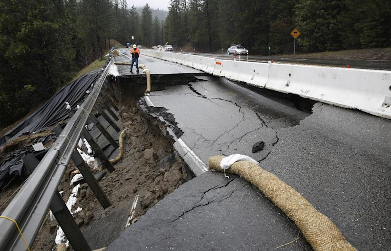 FILE--In this Feb. 21, 2017, file photo, the shoulder and one lane of westbound Highway 50 are damaged due to storms near Pollock Pines, Calif. The bill to repair California's roadways hammered by floods and rockslides in an onslaught of storms this winter is already at least $550 million, more than double what the state budgeted for such emergencies. (AP Photo/Rich Pedroncelli, file)
