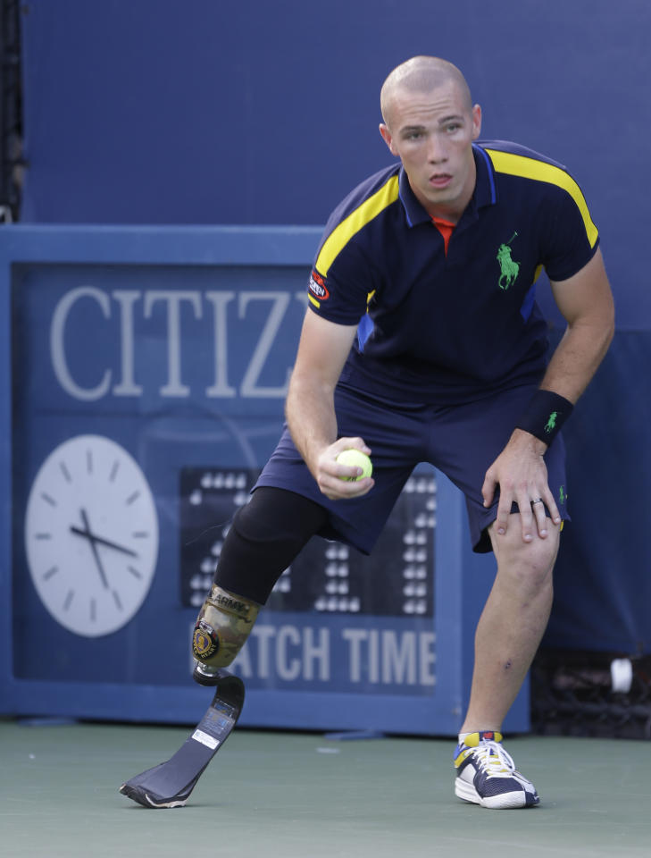 Ryan McIntosh picks up a ball while working a match in the second round of play at the 2012 US Open tennis tournament,  Wednesday, Aug. 29, 2012, in New York. (AP Photo/Darron Cummings)