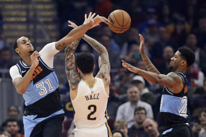 Cleveland Cavaliers' John Henson (31) knocks the ball loose from New Orleans Pelicans' Lonzo Ball (2) into the hands of Alfonzo McKinnie (28) during the first half of an NBA basketball game Tuesday, Jan. 28, 2020, in Cleveland. (AP Photo/Tony Dejak)