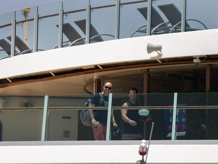 This image shows two passengers on a cruise ship deck.