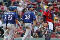 Texas Rangers' DJ Peters (38) and Nathaniel Lowe, left, walk to the dugout behind Boston Red Sox's Christian Vazquez, right, after scoring on a ground-rule double by Andy Ibanez during the ninth inning of a baseball game, Monday, Aug. 23, 2021, in Boston. (AP Photo/Michael Dwyer)