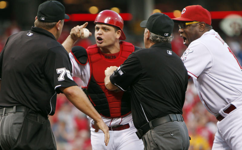 Cincinnati Reds catcher Devin Mesoraco yells at home plate umpire Chad Fairchild (75) as head coach Dusty Baker, right, steps in to pull him back after Mesoraco was ejected for arguing balls and strikes in the third inning of a baseball game against the San Diego Padres, Monday, July 30, 2012, in Cincinnati. (AP Photo/The Cincinnati Enquirer, Amanda Davidson)  MANDATORY CREDIT;  NO SALES