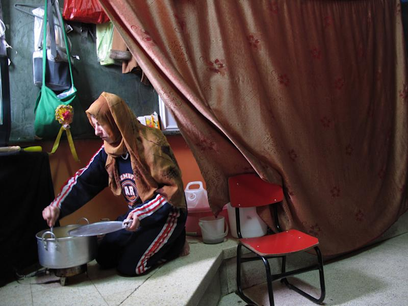 A Syrian woman driven from her home by fighting in Syria's civil war cooks a meal in her room in an elementary school that has been turned into a shelter in Damascus Syria, Thursday, Dec. 5, 2013. Around 44 families live in the school, just one set up as Syria deals with more than 5 million displaced people on its soil. (AP Photo/Lee Keath)