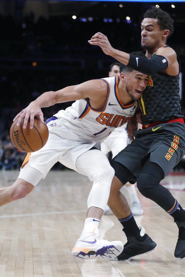 Phoenix Suns guard Devin Booker (1) drives against Atlanta Hawks guard Trae Young (11) in the first half of an NBA basketball game Tuesday, Jan. 14, 2020, in Atlanta. (AP Photo/John Bazemore)