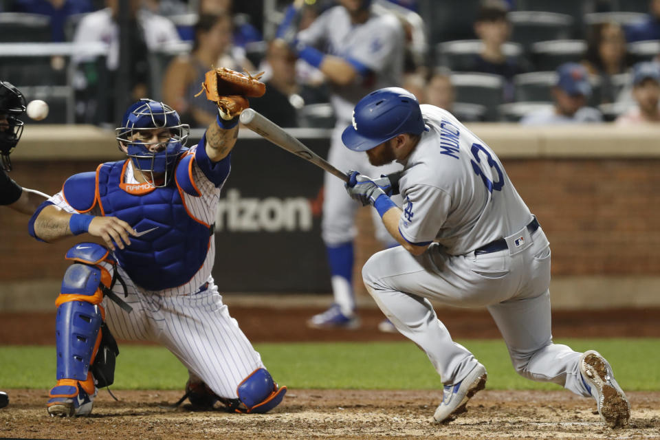 The ball whizzes past New York Mets catcher Wilson Ramos, left, as Los Angeles Dodgers' Max Muncy (13) ducks to avoid a high pitch in the eighth inning of a baseball game, Sunday, Sept. 15, 2019, in New York. (AP Photo/Kathy Willens)