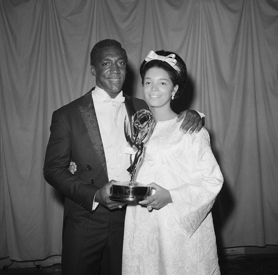 """Bill Cosby cohosted the 1966 Emmy Awards telecast, the first black actor/performer ever to do so.  At the time, the Awards were bicoastal, so Cosby hosted from New York, with fellow host Danny Kaye stationed in LA.  He also won an Emmy that night for Best Actor in A Dramatic Series—for his role in I Spy.  With I Spy, Cosby became the first African-American to co-star in a dramatic TV series and NBC the first network to green-light a series so cast.  Cosby and NBC worried that some affiliates might not carry the show, and indeed four stations—in Georgia, Florida, and Alabama—turned it down.  But the rest of America fell in love with witty Cosby and fellow international secret agent Robert Culp.  The show was a ratings hit, earning Cosby his first of three consecutive Emmy Awards.  In his acceptance speech, the courageous comedian graciously recognized the courage in others…""""I would also like to thank NBC for having GUTS.  I would like to thank Art Stark and Johnny Carson for presenting me each and every night on the `Tonight Show.'""""  Cosby hosted the Emmy's two more times (in 1969 and 1970) and grew to become a TV legend.  Bill Cosby with his wife Camille hold award presented May 22, 1966 after he was named the TV Emmy winner for his work in series, """"I Spy"""" in New York City. (AP Photo/David Pickoff)"""