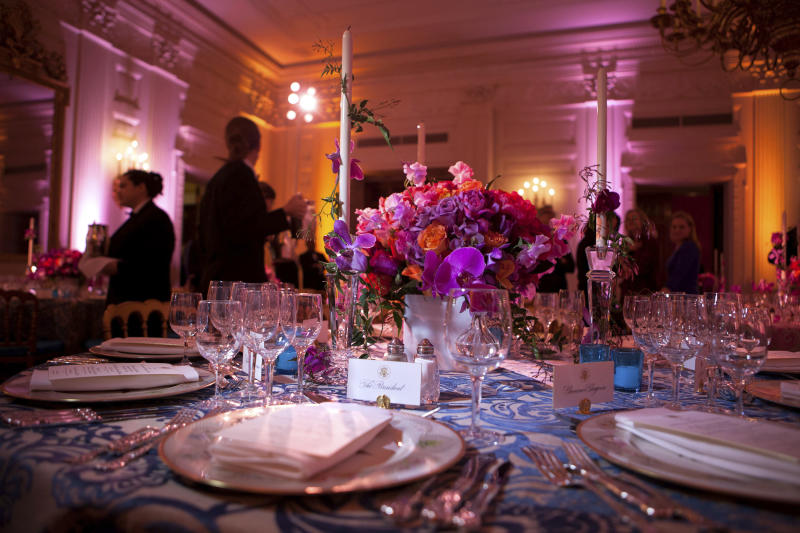 """In this Feb. 27, 2011 photo provided by Stichting Kunstboek, a vivid bouquet of orange and fuchsia flowers with accents of hot pink phaleonopsis orchids makes a strong statement for the annual National Governors Association Dinner at the White House state dining room in Washington. The historic """"Charleston"""" candlesticks are wrapped with blooming jasmine vine. The Lady Bird and President Johnson china service, featuring wildflowers from across America, reflects the gathering of Governors from all 50 states. The photograph is featured in the book """"Floral Diplomacy: At the White House,"""" by Laura Dowling. (Chuck Kennedy/The White House/Stichting Kunstboek via AP)"""